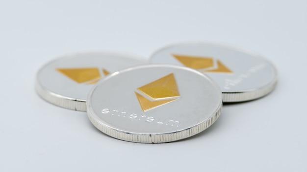 Monnaie ethereum argent métal physique sur mur blanc. nouvel argent virtuel sur internet dans le monde entier. cyberespace numérique etherum, crypto-monnaie eth. bon investissement futur du paiement en ligne