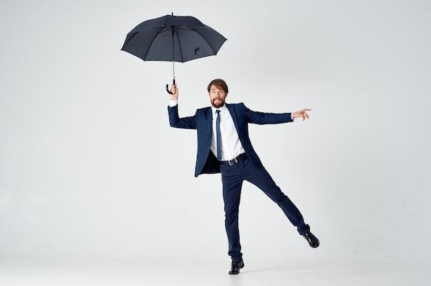 Un monsieur avec un parapluie ouvert dans un costume sombre penché sur le côté