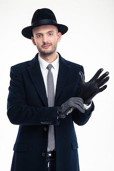 Monsieur séduisant en chapeau noir et manteau mettant des gants en cuir noir sur un mur blanc