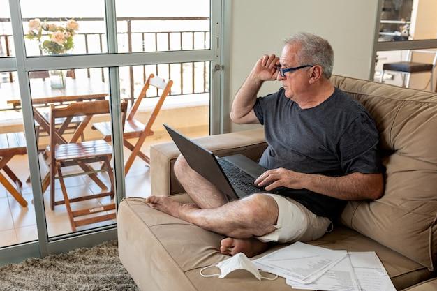 Monsieur tapant sur un ordinateur portable, travaillant à la maison dans un système de bureau à domicile en période de pandémie par le virus covid-19. lord travaille à la maison en portant des vêtements légers et avec le masque facial posé à côté.