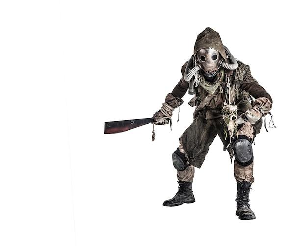 Monstre humanoïde agressif et maléfique ou créature post-apocalyptique, empoisonné par un monde dangereux de la pollution portant des chiffons en lambeaux et un masque à gaz, brandissant une prise de vue en studio à la machette tachée de sang sur blanc