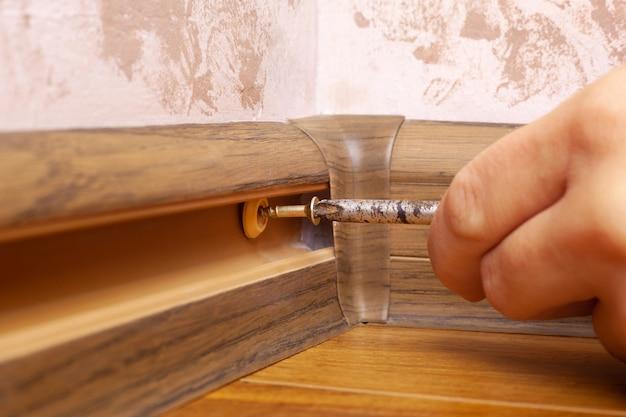 Montage et installation du socle, le maître installe la plinthe