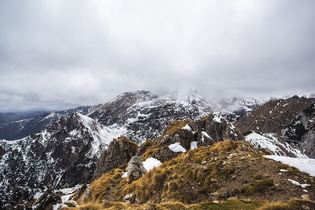 Montagne brune et blanche sous un ciel nuageux
