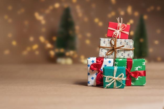 Une montagne de cadeaux dans le contexte des lumières de noël et des arbres