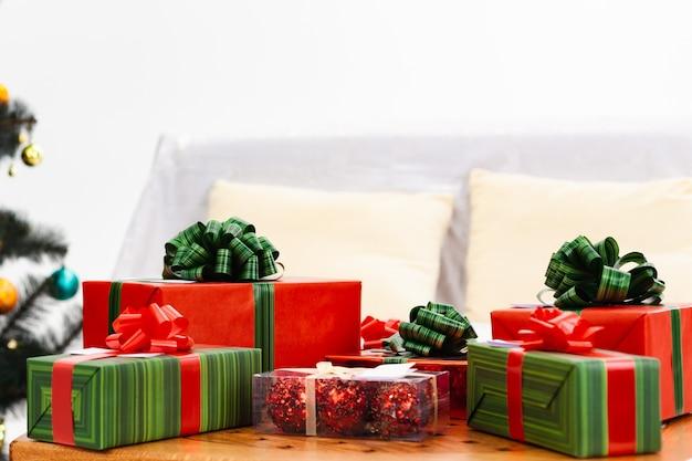 Une montagne de cadeaux en papier d'emballage rouge et vert sur une table basse