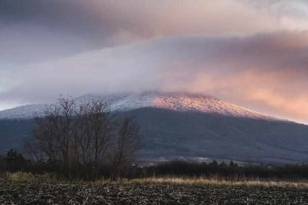 Montagne couverte de neige et un ciel nuageux pendant le coucher du soleil