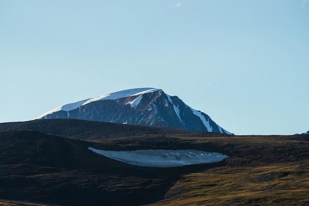 Montagne enneigée géante derrière la colline verte avec gros morceau de grand glacier sous le ciel bleu