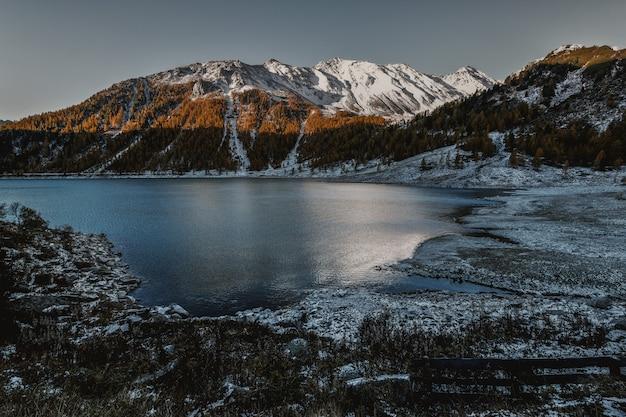 Montagne de grande hauteur brune et blanche à côté d'un plan d'eau