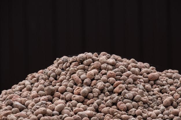 Une montagne de granules d'argile expansée d'argile sur un fond brun foncé