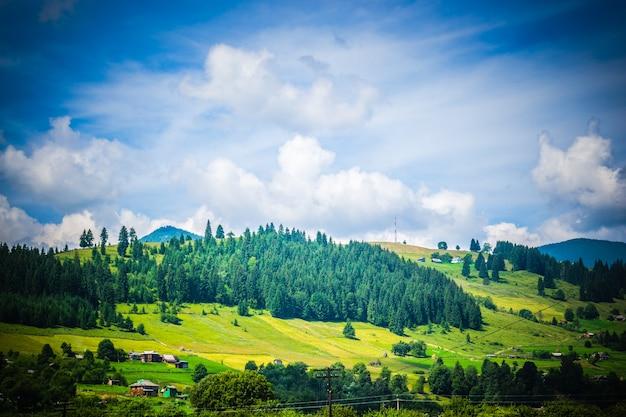 Montagne sur laquelle pousse la forêt d'épinettes et le ciel avec des nuages blancs