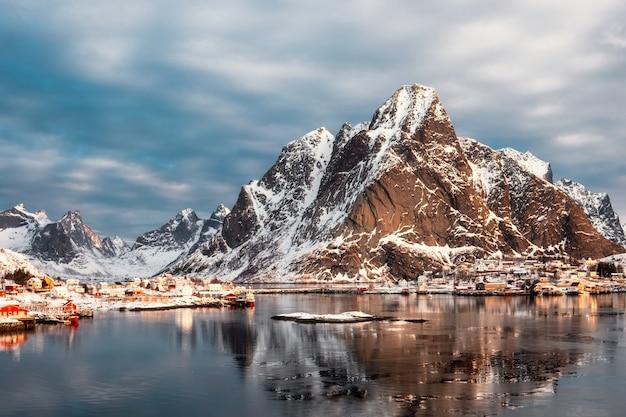 Montagne de neige avec village scandinave sur l'océan arctique en hiver