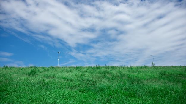 Une montagne avec une pelouse verte a le ciel comme arrière-plan