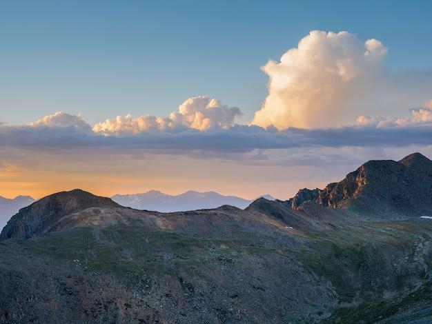 Montagne rocheuse dans le ciel nuageux de l'aube. paysage de montagne minimal atmosphérique avec ciel d'aube lilas. paysage minimaliste pittoresque avec coucher de soleil violet dans les montagnes. silhouettes de montagnes sur fond.