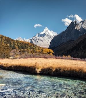 Montagne sacrée de chana dorje avec prairie dorée et rivière de cristal
