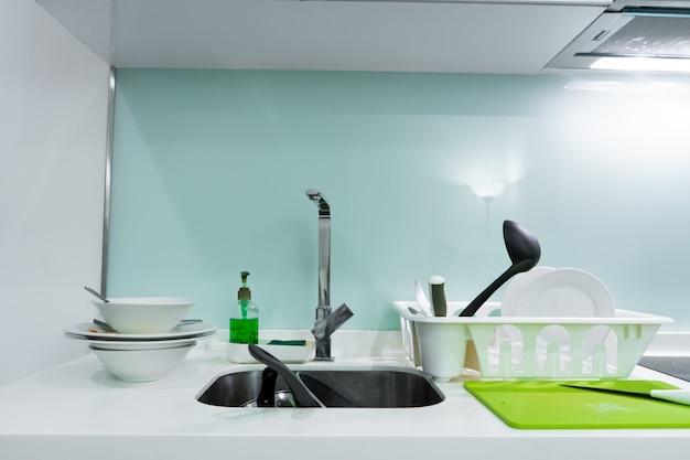 Une montagne de vaisselle sale dans l'évier de la cuisine. désordre dans la maison