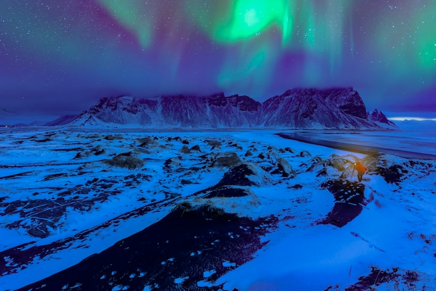 Montagne de vestrahorn sur le cap de stokksnes avec des aurores boréales vertes et des reflets. incroyable paysage marin de la nature islandaise. lieu emblématique pour les photographes paysagistes et les blogueurs. image panoramique de l'islande