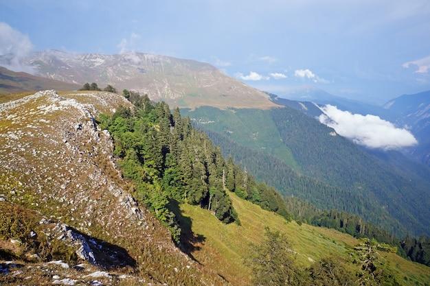 Les montagnes de l'abkhazie en été journée ensoleillée, vue de haut en bas. les pics du caucase au-dessus des nuages.