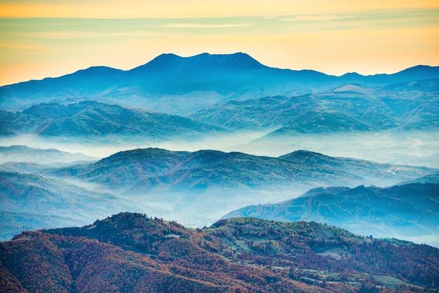 Montagnes bleues au coucher du soleil avec brume blanche sur les collines