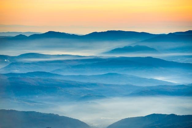 Montagnes et collines bleues sous le beau coucher du soleil orange