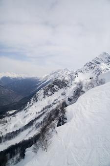 Montagnes dans la neige contre le ciel dans les nuages