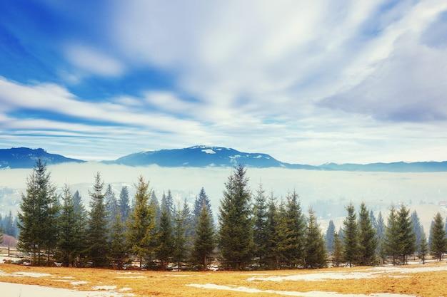 Montagnes enneigées dans la brume. le début du printemps