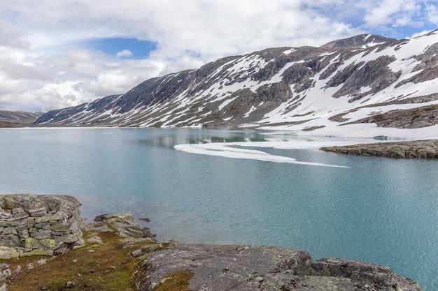 Montagnes enneigées entourées de nuages dans le fjord norvégien reflet dans l'eau