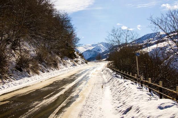 Montagnes enneigées et paysage routier à gudauri, géorgie. journée ensoleillée.