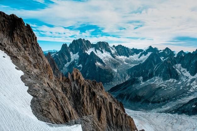 Montagnes enneigées sous un ciel nuageux