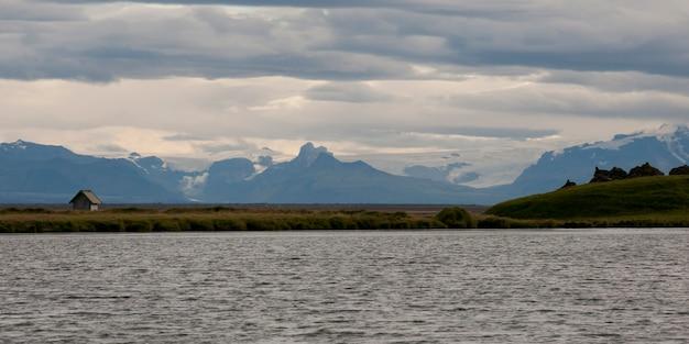 Montagnes et glaciers d'islande, avec des prairies et un hangar, du littoral
