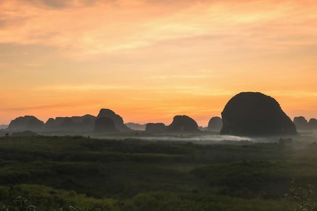 Montagnes karstiques calcaires de silhouette et brouillard de mouvement à l'aube avant le lever du soleil depuis le point de vue de din daeng (dang) doi dans la province de krabi, en thaïlande. destination de voyage célèbre dans le sud de la thaïlande ou du siam.