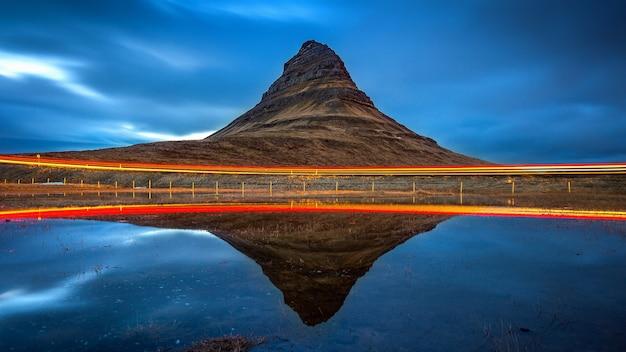Montagnes kirkjufell et réflexion avec lumière de voiture, islande.