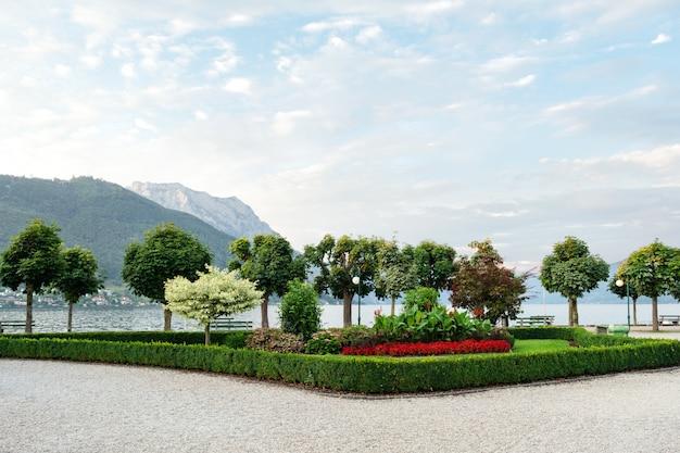 Les montagnes, le lac et la digue de la ville avec des arbres taillés, des arbustes et des parterres de fleurs.