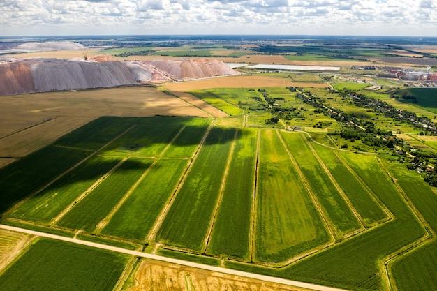 Montagnes de produits pour la production de sel de potasse et d'un champ vert. montagnes de sel près de la ville de soligorsk. production d'engrais pour la terre. biélorussie.