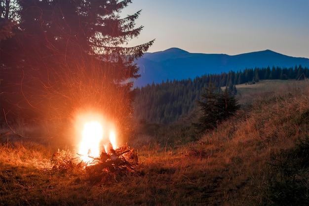 Montagnes le soir avec un feu de joie avec des étincelles devant