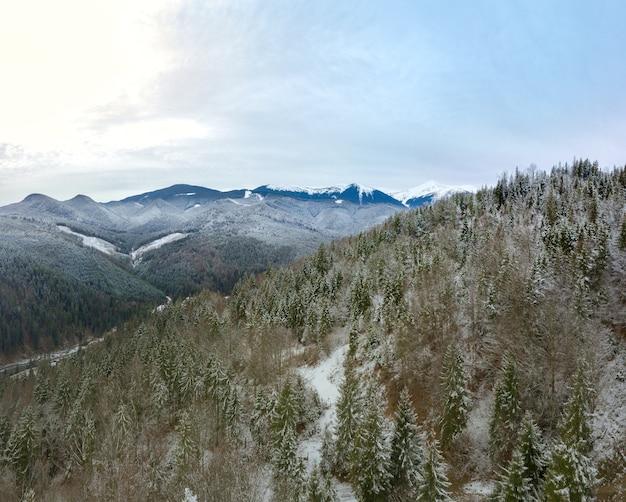 Les montagnes sont couvertes de forêt. première neige au sol et sur les branches.