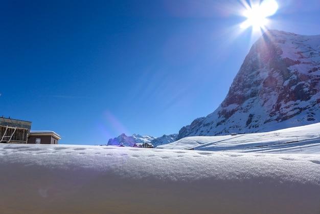 Les montagnes sont couvertes de neige sur fond de ciel bleu et soleil