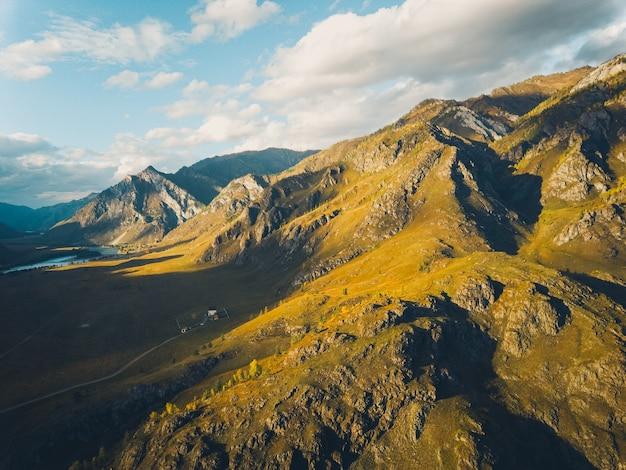Montagnes texturées jaune vif contre un ciel bleu, vue aérienne. le coucher du soleil. tir de drone