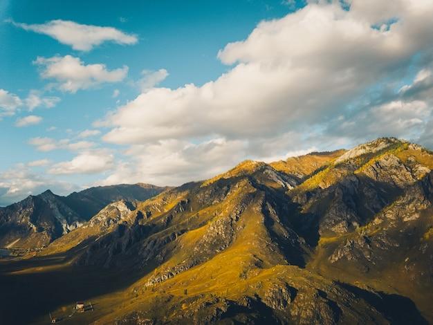 Montagnes texturées jaune vif contre un ciel bleu, vue aérienne drone shot