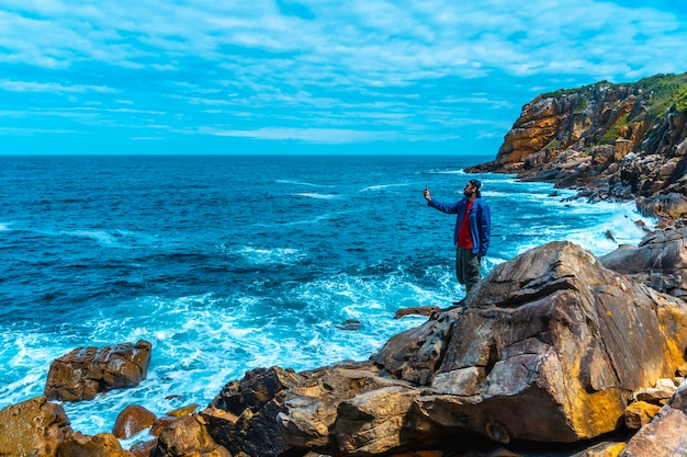 Monte ulia dans la ville de san sebastián, pays basque. visitez la crique cachée de la ville appelée illurgita senadia ou illurgita senotia. un jeune homme dans une veste bleue dans l'anse en prenant une photo