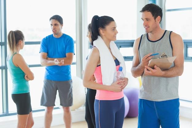 Monter le couple avec des amis en arrière-plan dans la salle d'exercice