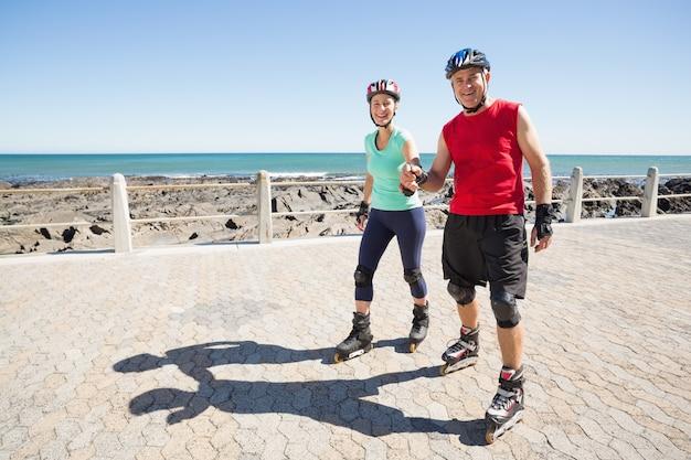 Monter le couple mature rollerblading sur la jetée
