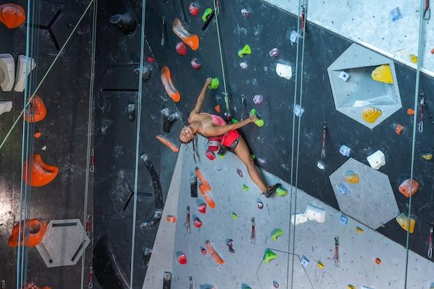 Monter la femme blonde tenant par l'un des petits rochers sur le mur d'escalade tout en pratiquant un sport extrême dans la salle de gym