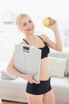 Monter la femme dans sportswear tenant la balance et la pomme dans le studio de remise en forme