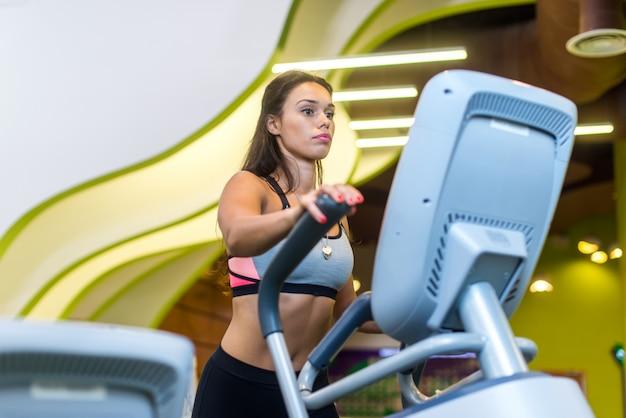 Monter la femme faisant du cardio dans un vélo elliptique dans une salle de sport.