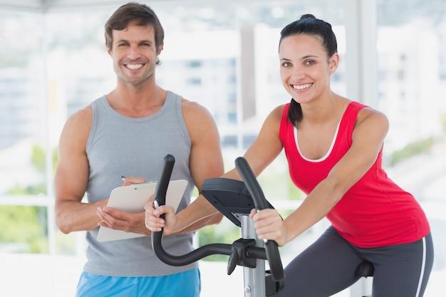 Monter une femme avec un instructeur de sexe masculin travaillant à la classe de spinning dans une salle de gym lumineuse
