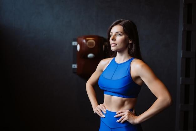 Monter la femme posant sur l'appareil photo. entraîneur personnel montrant sa forme. beauté du sport moderne.