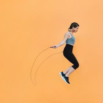 Monter la femme sautant avec une corde