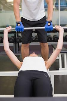 Monter la femme soulevant des haltères avec ses taches d'entraîneur
