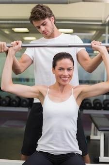 Monter la femme souriante soulevant des haltères avec ses taches d'entraîneur