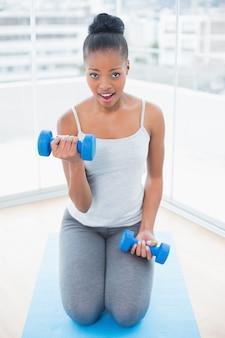 Monter la femme en vêtements de sport assis sur un tapis d'exercice et de travailler avec haltère